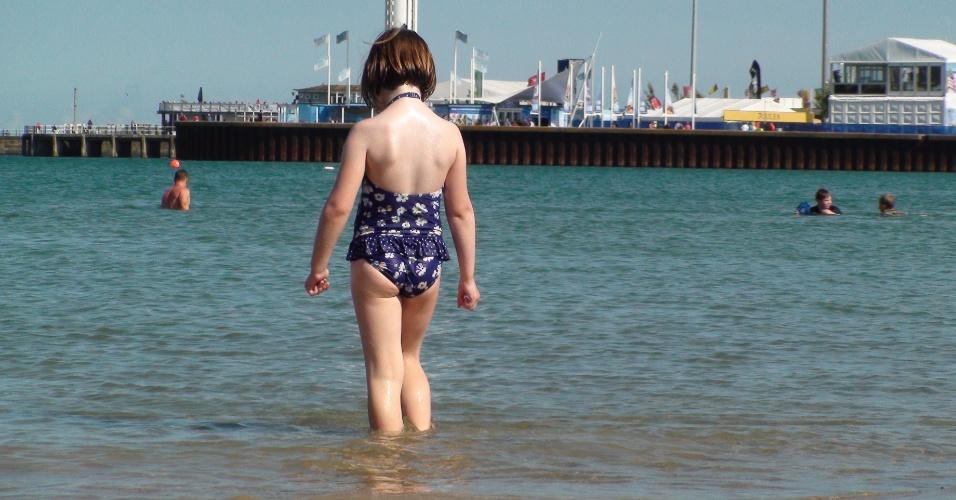 Menina se aventura nas águas geladas do canal da Mancha; a maioria dos veranistas fica na areia e vestidos com agasalhos