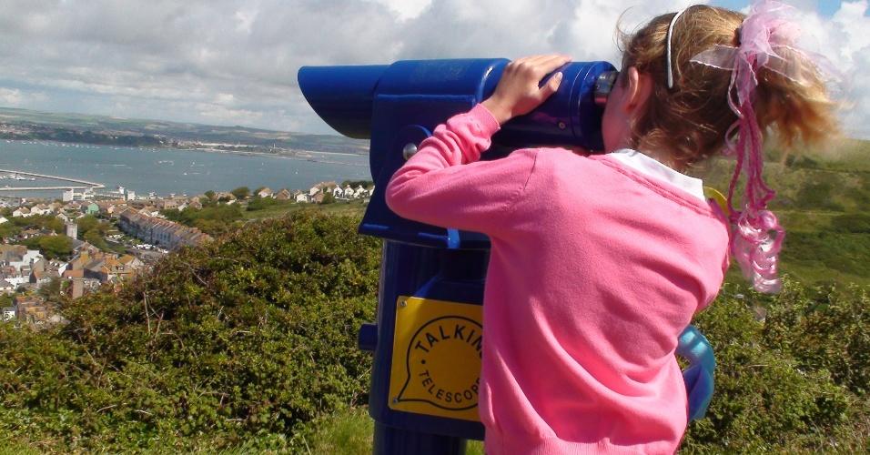 Menina tenta visualizar a competição através de um telecóspio oferecido um serra da cidade de Portland