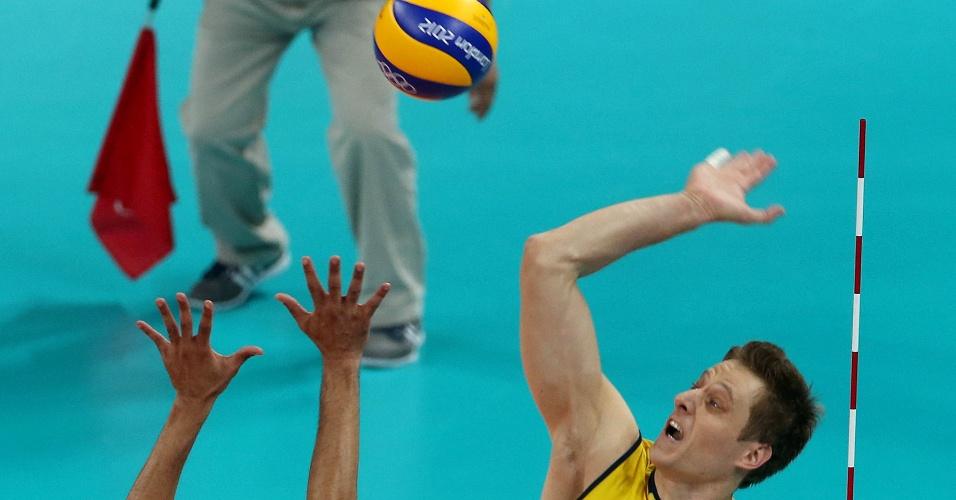 Murilo, ponta da seleção de vôlei, ataca contra o bloqueio da Tunísia, na estreia do Brasil na Olimpíada