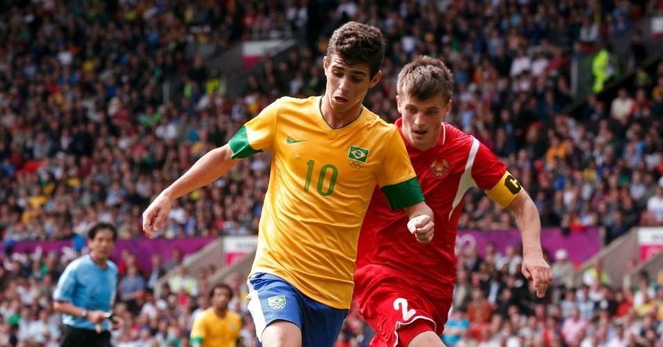 Oscar avança com a bola observado de perto por defensor de Belarus