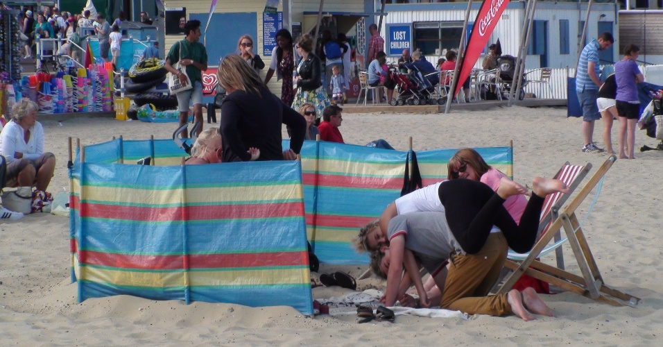 Para evitar a areia levada pelo vento forte em Weymouth, família monta cercadinho em torno de seu pertences na praia