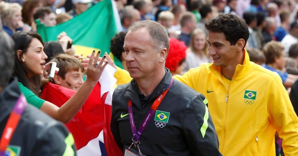 Seguido por Ganso, técnico Mano Menezes se dirige ao banco de resevas antes do início do jogo contra Belarus