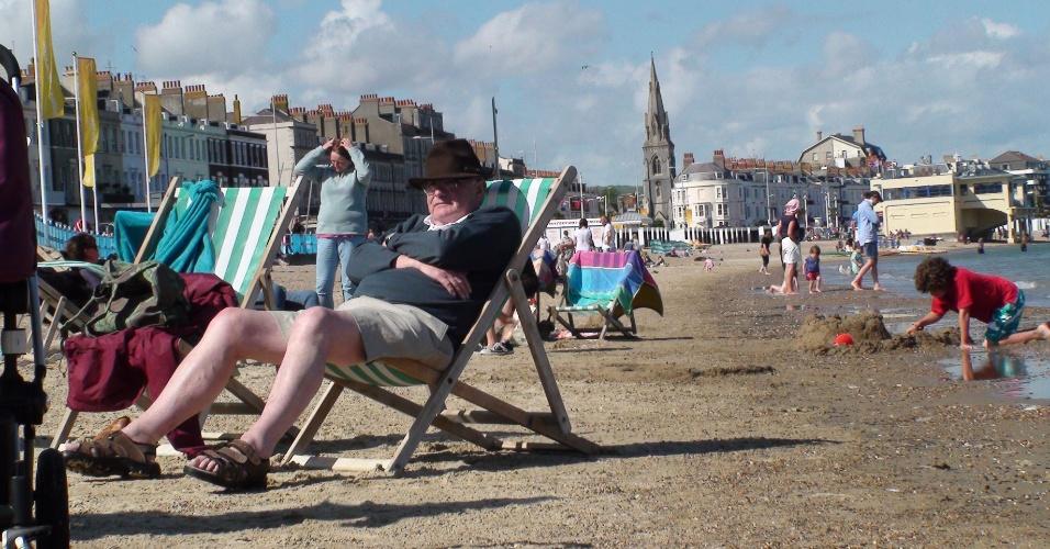 Senhor aproveita o sol do entardecer na praia de Weymouth, onde acontecem competições do iatismo olímpico