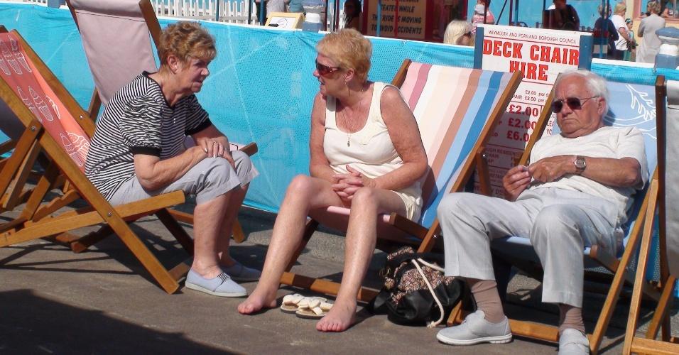 Grupo de idosos aproveitam o inconstante sol inglês para se bronzear no calçadão de Weymouth, desse do iatismo olímpico