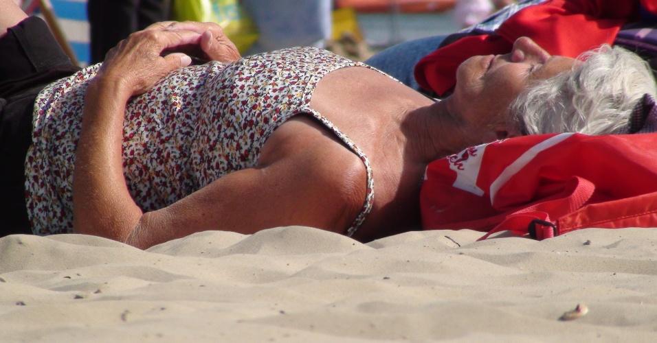 Senhora toma sol na parte da praia de areia fina de Weymouth, na costa inglesa diante do canal da Mancha
