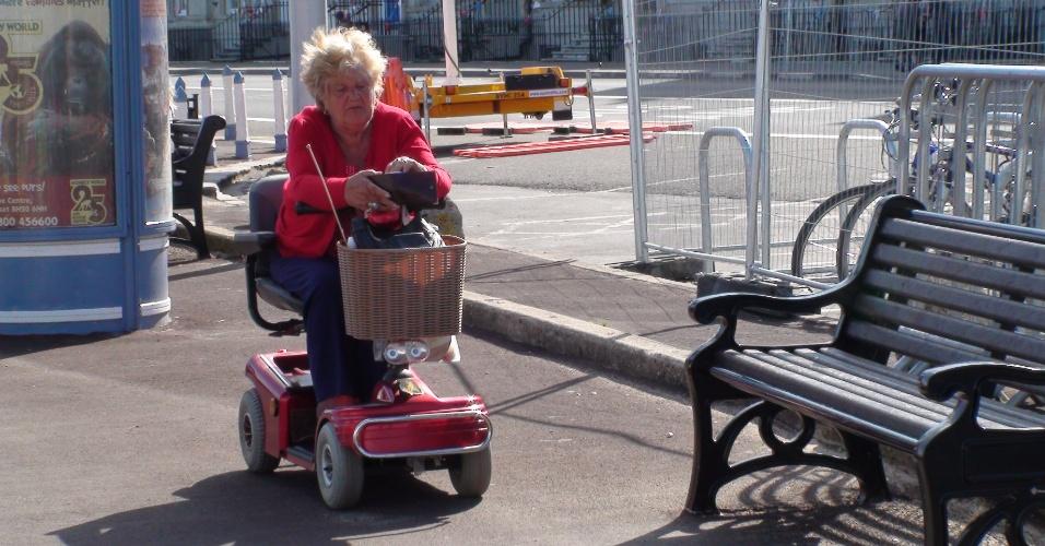 Senhora usa cadeira de roda elétrica para se locomover no calçadão da cidade litorânea de Weymouth