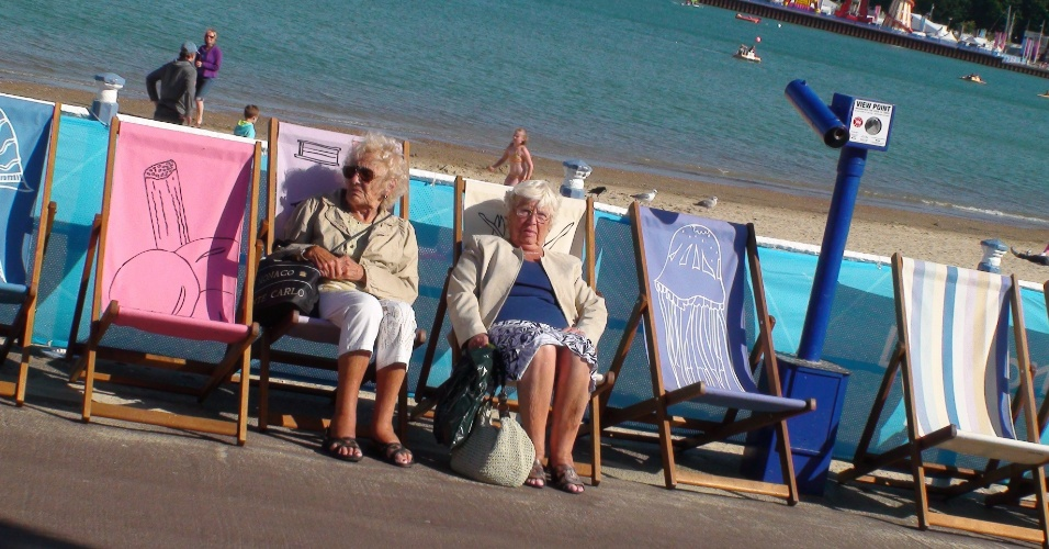 Senhoras tomam sol em cadeira no calçadão da praia de Weymouth, costa do condado de Dorset