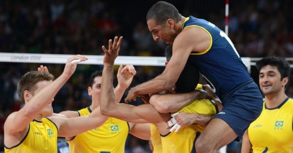 Serginho pula em cima de Wallace para comemorar ponto da seleção brasileira no jogo contra a Tunísia