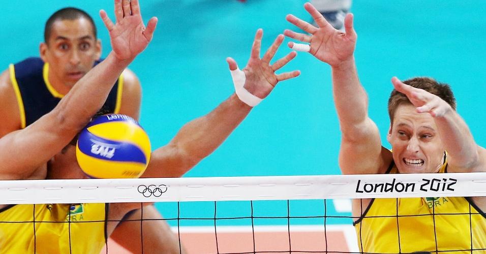 Sidão e Murilo, da seleção de vôlei, tentam o bloqueio em ataque da Tunísia, na Olimpíada