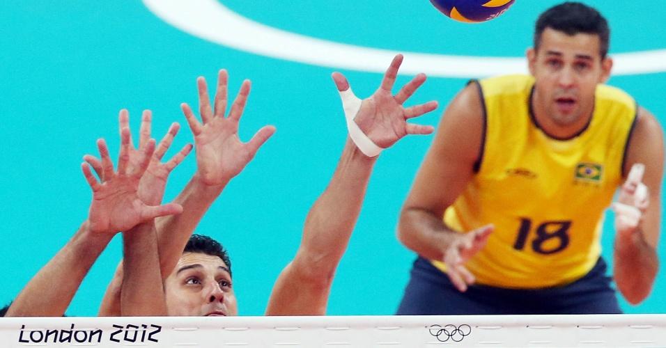 Sidão tenta alcançar a bola em bloqueio no jogo contra a Tunísia, enquanto Dante observa a jogada