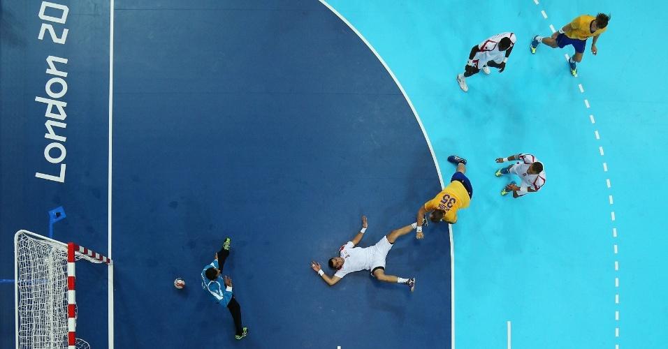 Sueco Andreas Nilsson supera a marcação da Tunísia em lance de jogo do handebol masculino (29/07/2012)