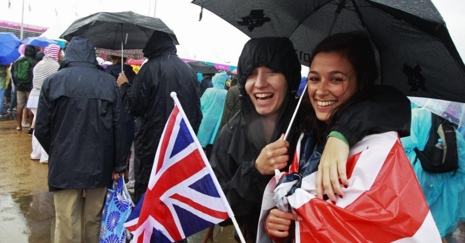 Torcedoras se protegem da chuva durante o segundo dia oficial de Olimpíada, neste domingo