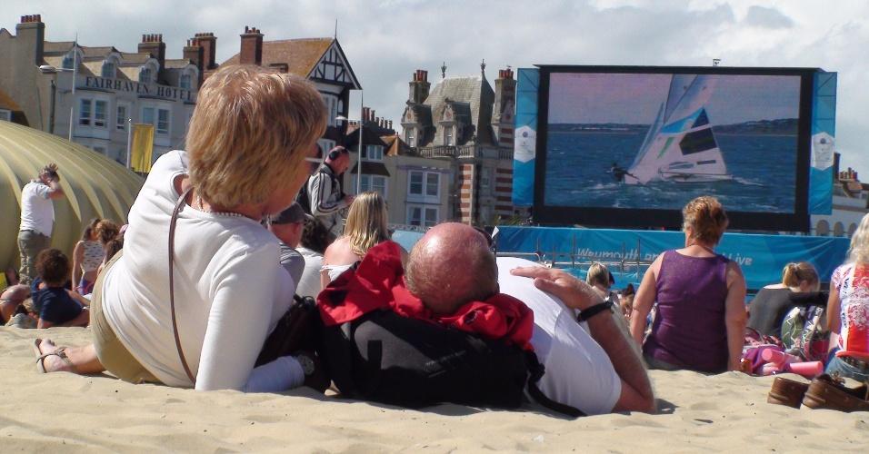 Veranistas em Weymouth acompanham o desempenho britânico no iatismo vendo telão montado na praia