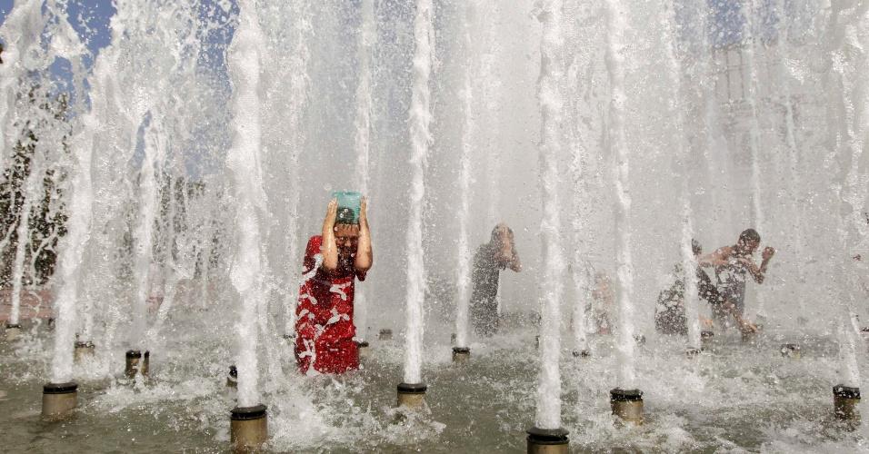 30.jul.2012 - Crianças se refrescam em fonte nesta segunda-feira (30) em Minsk, capital de Belarus. Termômetros tem registrado temperaturas acima de 30ºC durante o verão no país