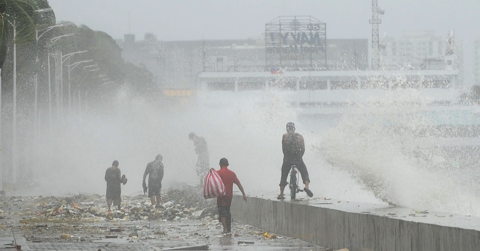 30.jul.2012 - Moradores se protegem da chuva nesta segunda-feira (30) em Manila, nas Filipinas. Fortes ventos e chuvas da tempestade tropical Saola atingiram o local
