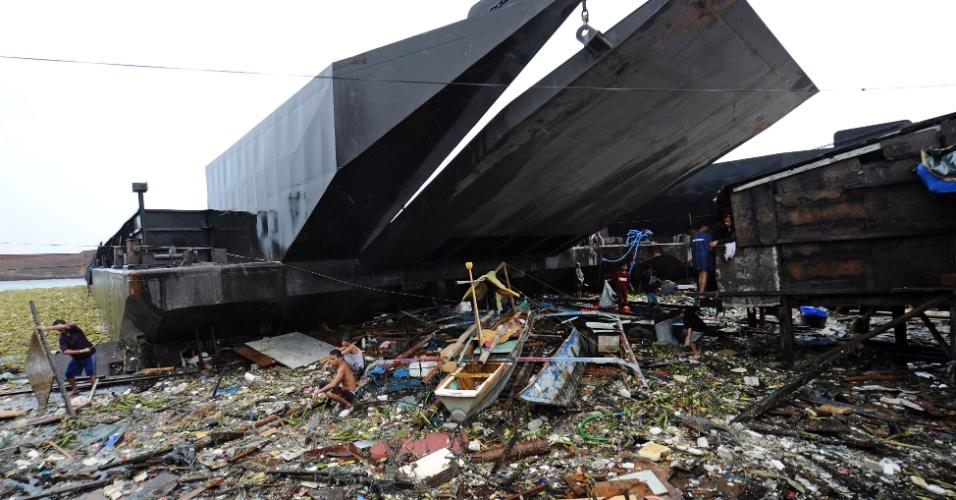 30.jul.2012 - Moradores tentam salvar pertences nesta segunda-feira (30) entre os destroços de suas casas em Manila, nas Filipinas. Fortes ventos e chuvas da tempestade tropical Saola levaram duas barcaças ao local. Ao menos uma pessoa morreu e milhões ficaram sem energia