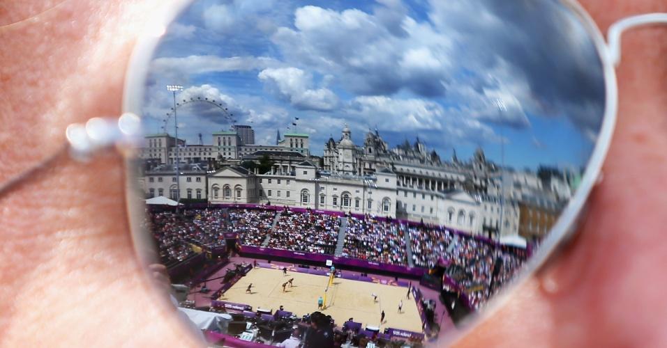 Arena de vôlei de praia é focalizada através de óculos escuros de torcedor