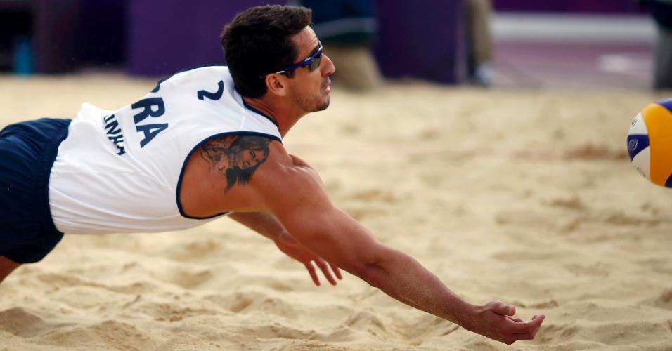 Brasileiro Pedro, do vôlei de praia, defende bola e exibe tatuagem no ombro em jogo contra dupla do Reino Unido