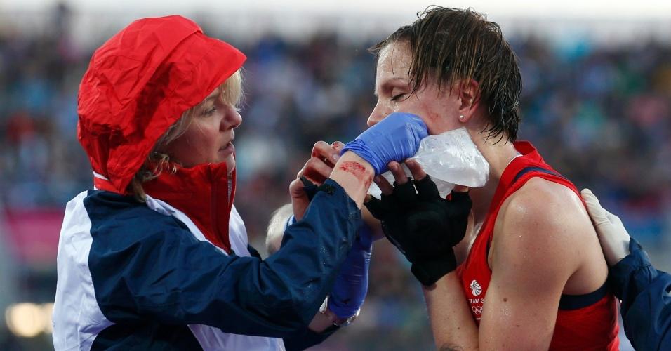 Britânica Kate Walsh recebe atendimento médico após ser atingida no rosto por taco de jogadora da seleção japonesa, durante partida do hóquei na grama feminino neste domingo