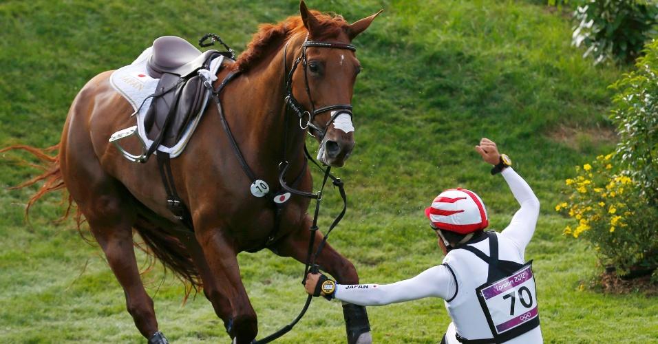 Japonesa Yoshiaki Oiwa cai do cavalo durente competição do hipismo de cross-country