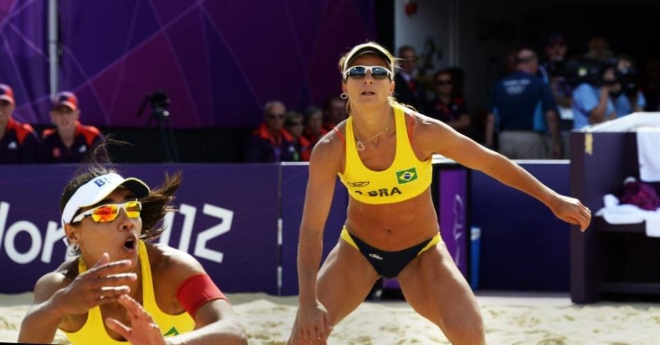 Larissa observa Juliana fazer defesa durante a vitória da dupla brasileira sobre alemãs, em Londres