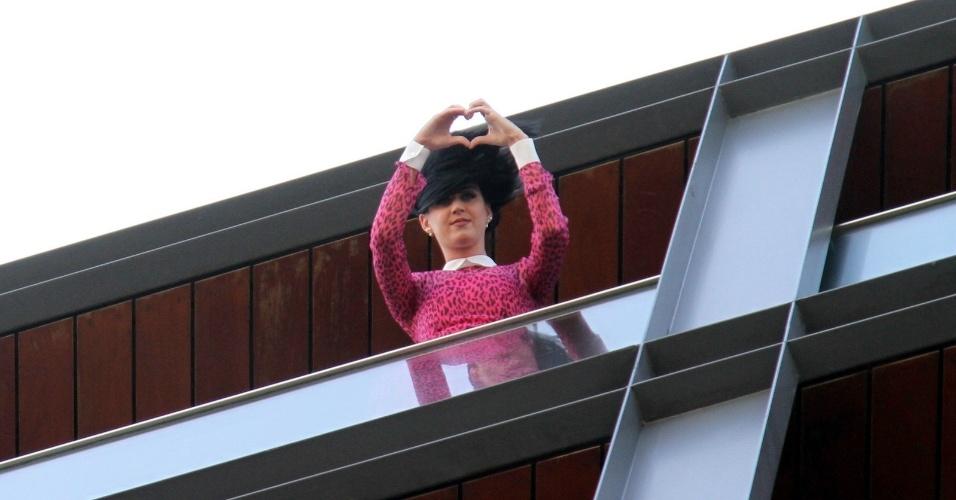 Na sacada do hotel em que está hospedada no Rio de Janeiro, Katy Perry faz coração para os fãs (30/7/12)