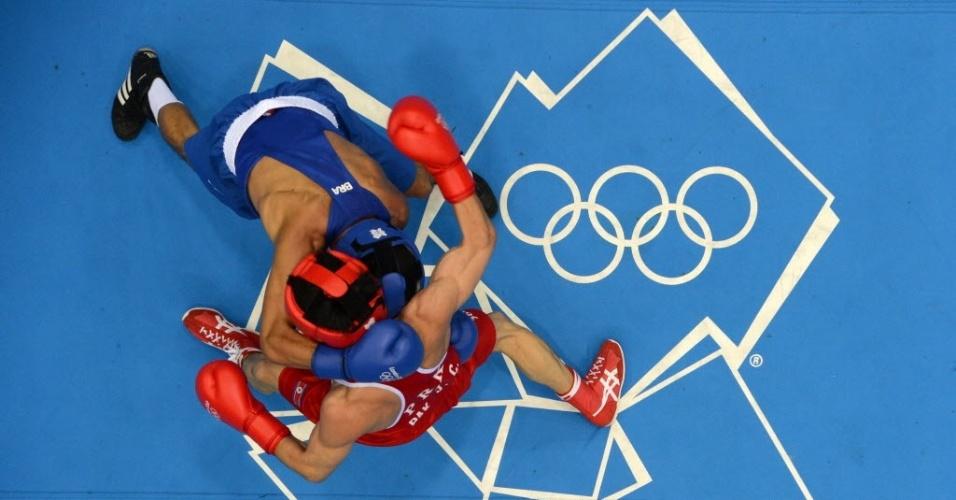 O boxeador brasileiro Julião Neto (azul) tenta o ataque contra o rival coreano