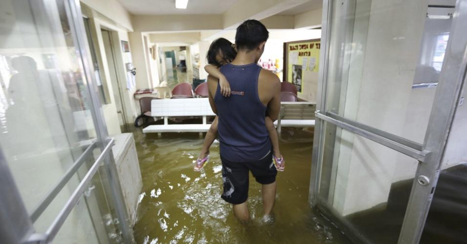 31.jul.2012 - Homem leva uma garota para receber atendimento em um hospital inundado de Valenzuela, ao norte da capital, Manila, nas Filipinas. A tempestade tropical Saola já fez pelo menos sete vítimas, segundo agências de notícias locais