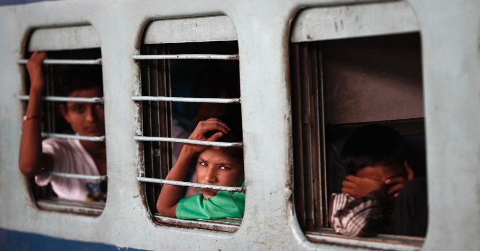 31.jul.2012 - Jovens passageiros sentados no interior de um vagão esperam a eletricidade ser restaurada em uma estação de trem em Nova Déli