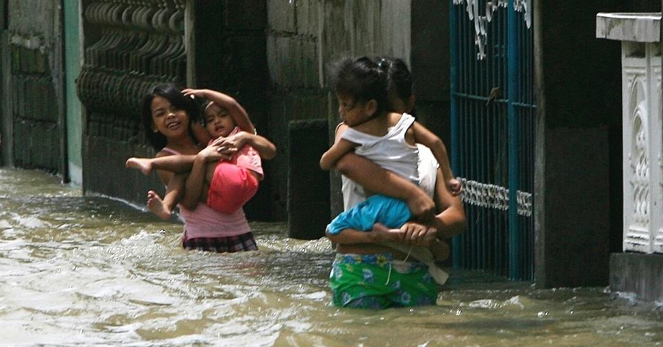 31.jul.2012 - Mães transportam os filhos pela enchente causada pelas chuvas de monções na cidade Almacen, no norte das Filipinas. A tempestade tropical Saola já fez pelo menos sete vítimas, segundo agências de notícias locais