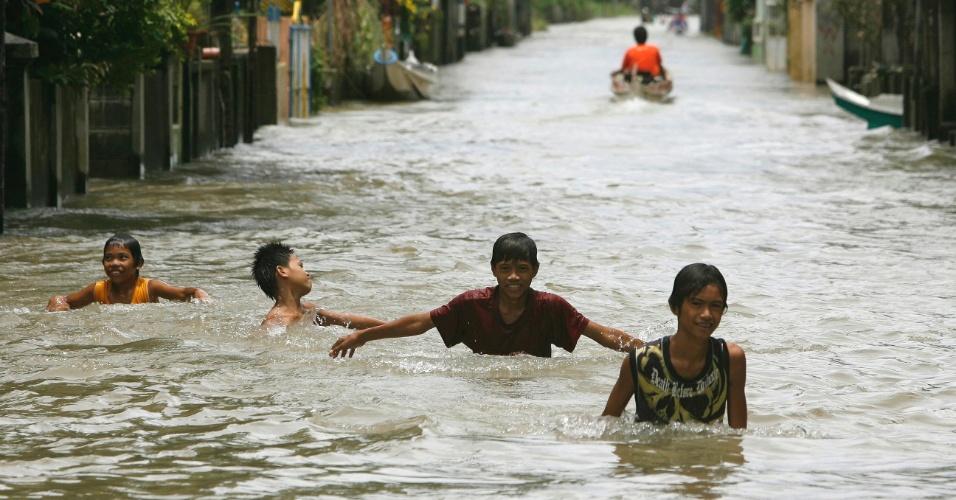 31.jul.2012 - Meninos brincam em rua alagada da cidade de Almacen, ao norte de Manila, nas Filipinias. A tempestade tropical Saola já fez pelo menos sete vítimas, segundo agências de notícias locais