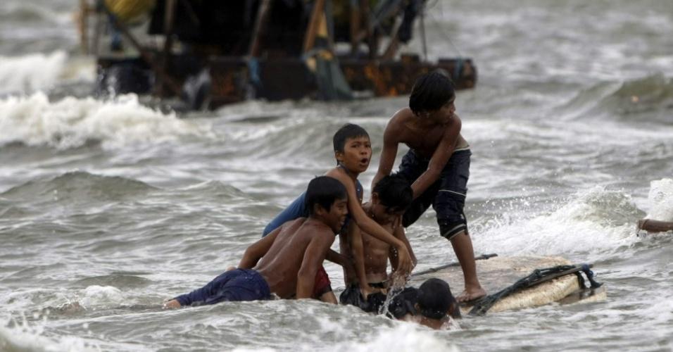 31.jul.2012 - Meninos navegam sobre uma balsa improvisada na Baía de Manila, capital das Filipinas. A tempestade tropical Saola já fez pelo menos sete vítimas, segundo agências de notícias locais