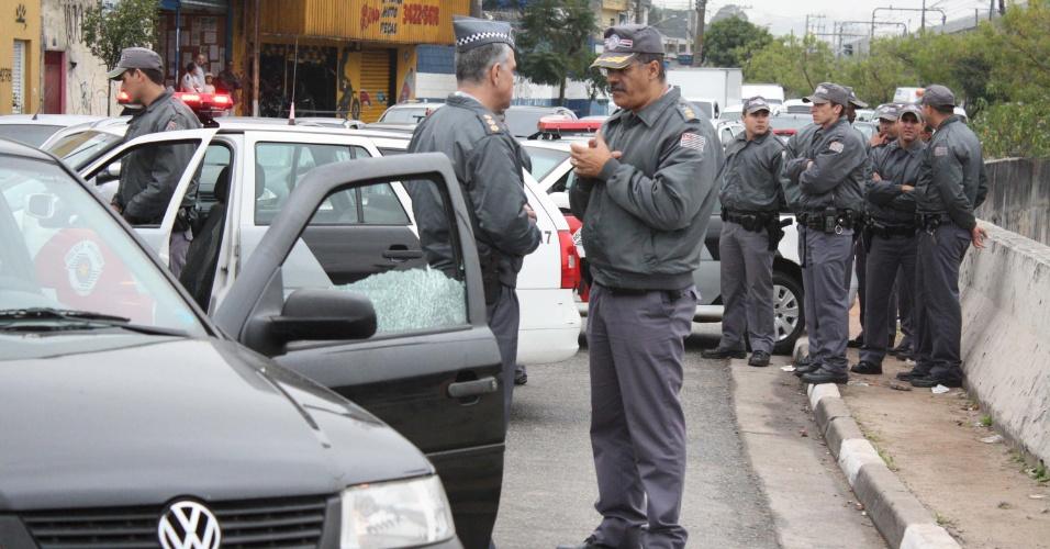 31.jul.2012 - Policias se aglomeram no local onde um soldado da PM foi morto a tiros, no Capão Redondo, zona sul de São Paulo, na manhã desta terça-feira (31). Quatro homens em uma moto dispararam vários tiros contra o carro do policial, que foi levado ao pronto-socorro do Campo Limpo, mas não resistiu aos ferimentos e morreu