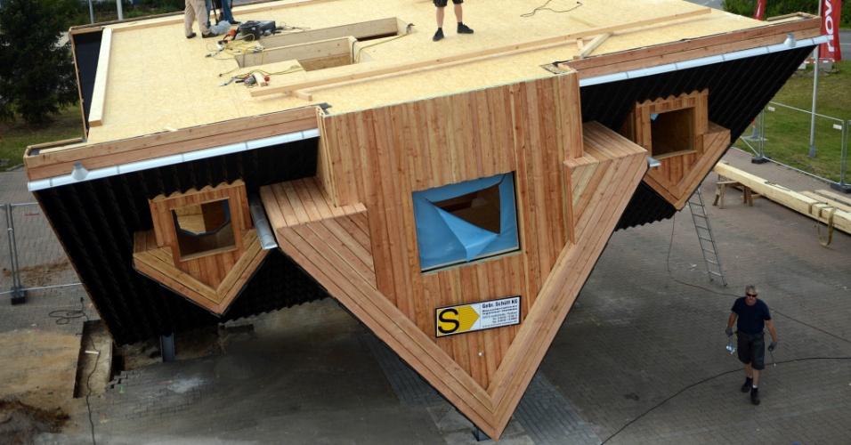 31.jul.2012 - Trabalhadores montam uma casa de cabeça para baixo no estacionamento de um shopping em Guenthersdorf, próximo de Leipzig, no leste da Alemanha. O imóvel, que terá dois andares, está programado para abrir em outubro de 2012