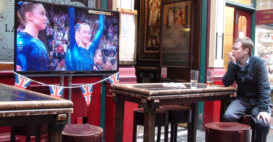 6ª parada: Cliente acompanha atentamente no telão do pub a apresentação da ginástica olímpica