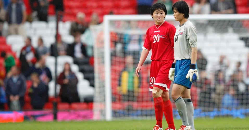 A camisa 20 Choe Yong-sim e a goleira O Chang-ran deixam o gramado após a derrota da seleção norte-coreana frente aos Estados Unidos