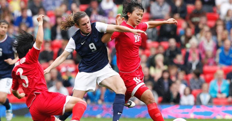 A norte-americana Heather O'Reilly disputa bola contra norte-coreanas, em jogo no Old Trafford