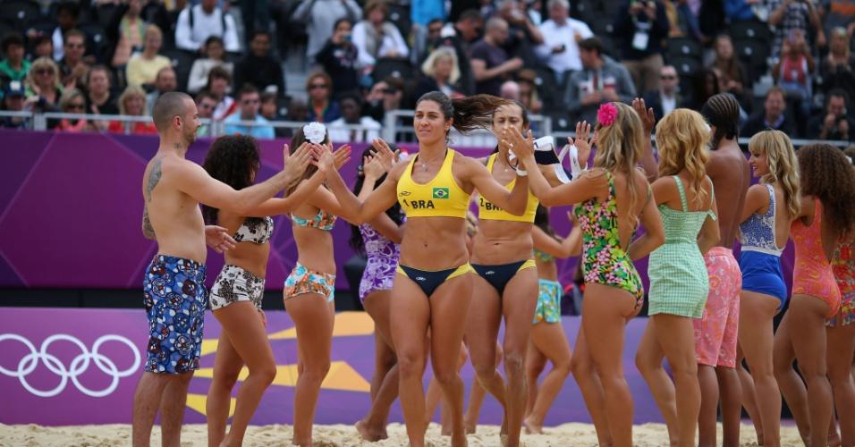 Brasileiras Maria Elisa e Talita cumprimentam cheerleaders ao entrar em quadra para jogo contra alemãs Sara Goller e Laura Ludwig