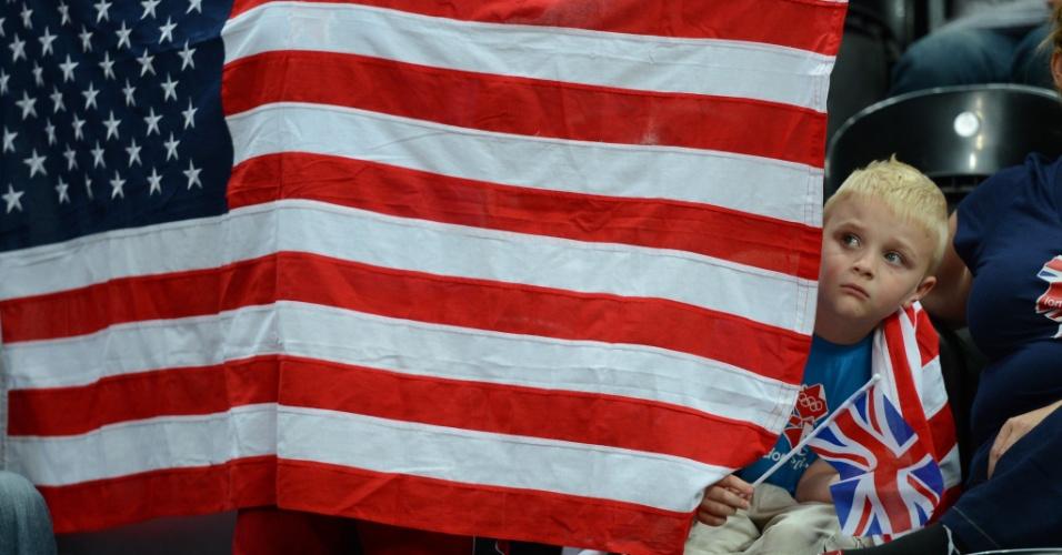Garoto fica escondido atrás da bandeira dos Estados Unidos antes de jogo entre Lituânia e Nigéria no basquete masculino em Londres (31/07/2012)