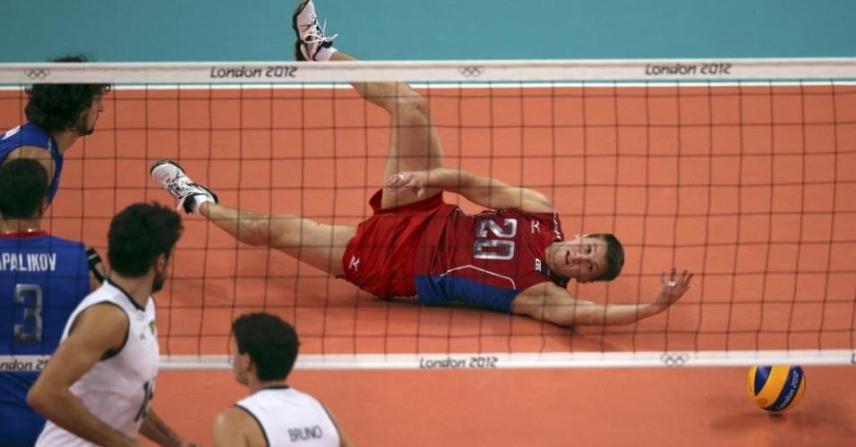 Jogador russo se atira no chão para pegar ataque de Lucão, meio de rede da seleção brasileira
