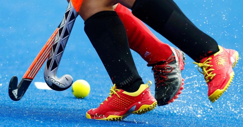 Sobre quadra molhada, jogadoras de China e Bélgica disputam bola em partida de hóquei na grama