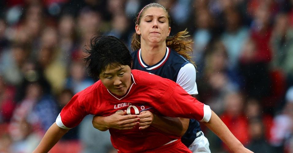 Zagueira norte-coreana Choe Yong Sim é agarrada por atacante norte-americana Alex Morgan, em duelo em Manchester