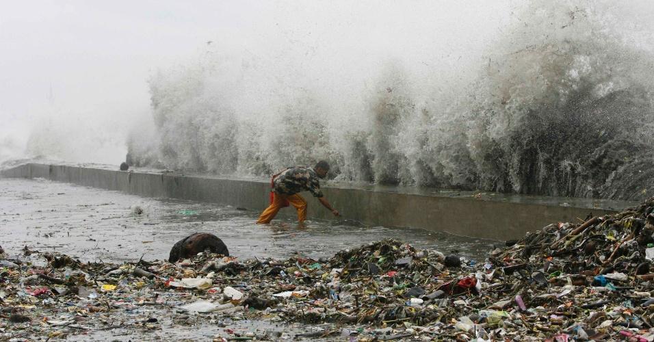 01.ago.2012 - Morador vasculha lixo em avenida alagada na baía de Manila, capital das Filipinas. O Sudeste Asiático enfrenta o período das monções, que causam chuvas intensas e alagamentos em diversas cidades da região