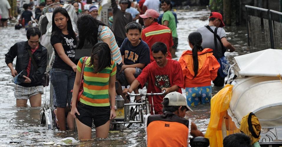 01.ago.2012 - Moradores de um subúrbio de Manila, capital das Filipinas, andam por rua alagada. Segundo agências de notícias, o número de mortes no país provocadas pela tempestade tropical Saola chegou a 12 e uma pessoa está desaparecida