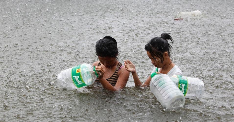 01.ago.2012 - Para comprar água potável, duas mulheres transportam garrafas plásticas vazias em rua alagada de Manila, capital das Filipinas. Agências de notícias informam que o número de mortos no país chegou a 12 e uma pessoa está desaparecida