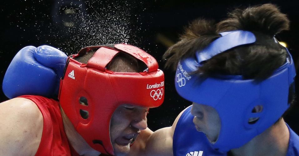 Água voa da cabeça de Tervel Pulev, peso pesado da Bulgária, depois de o pugilista ser atingido pelo chinês Xuanxuan Wang
