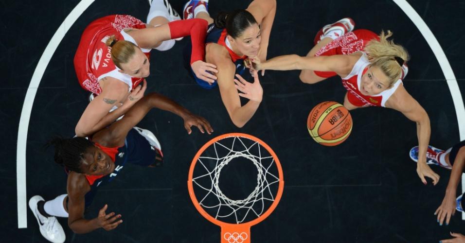 Atletas ads seleções de basquete do Reino Unido e da Rússia disputam bola no garrafão