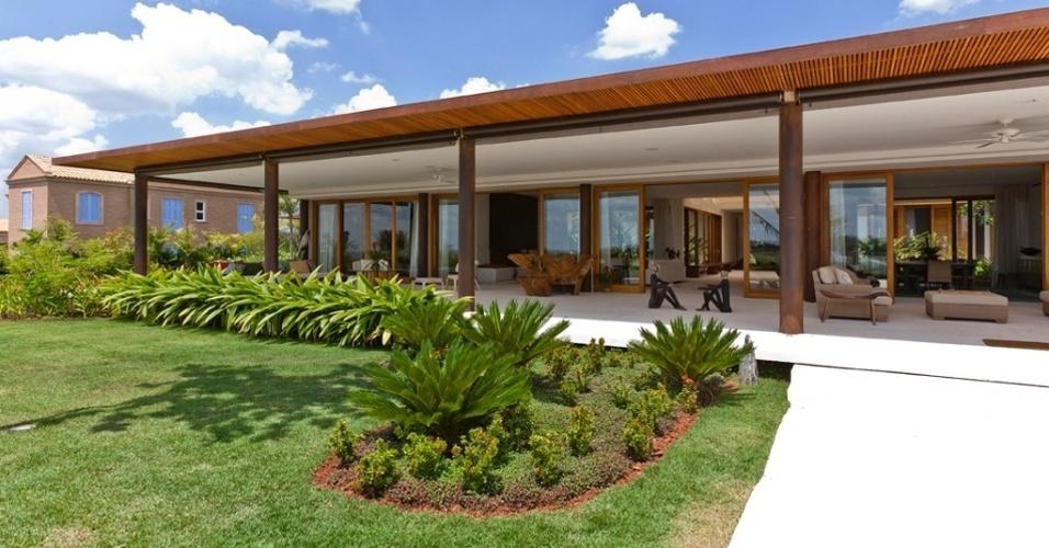 De frente para jardins exuberantes, a ampla varanda acompanha toda a fachada da porção social da Casa H, projetada pelo arquiteto Erick Figueira de Mello
