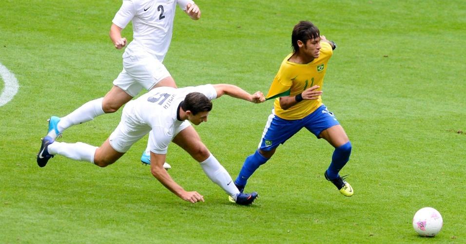 Defensor da Nova Zelândia tenta segurar Neymar pela camisa em partida desta quarta-feira