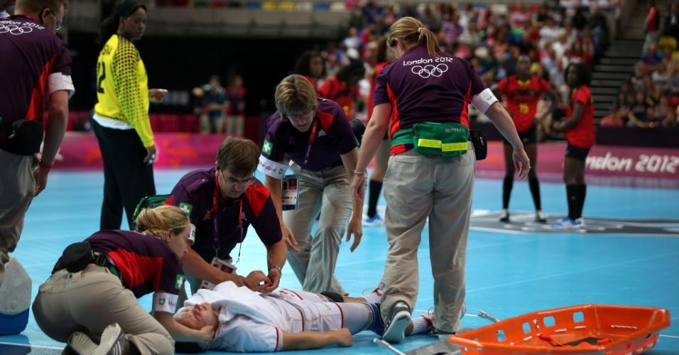 01.ago.2012 - Milena Knezevic recebe atendimento após se machucar durante partida de handebol contra Angola nas Olimpíadas de Londres